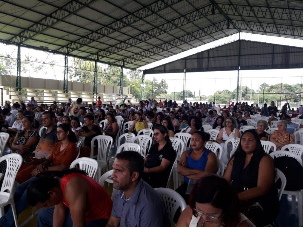 Cerca de 200 pessoas sentadas em cadeiras brancas assistem palestras em evento de educação.