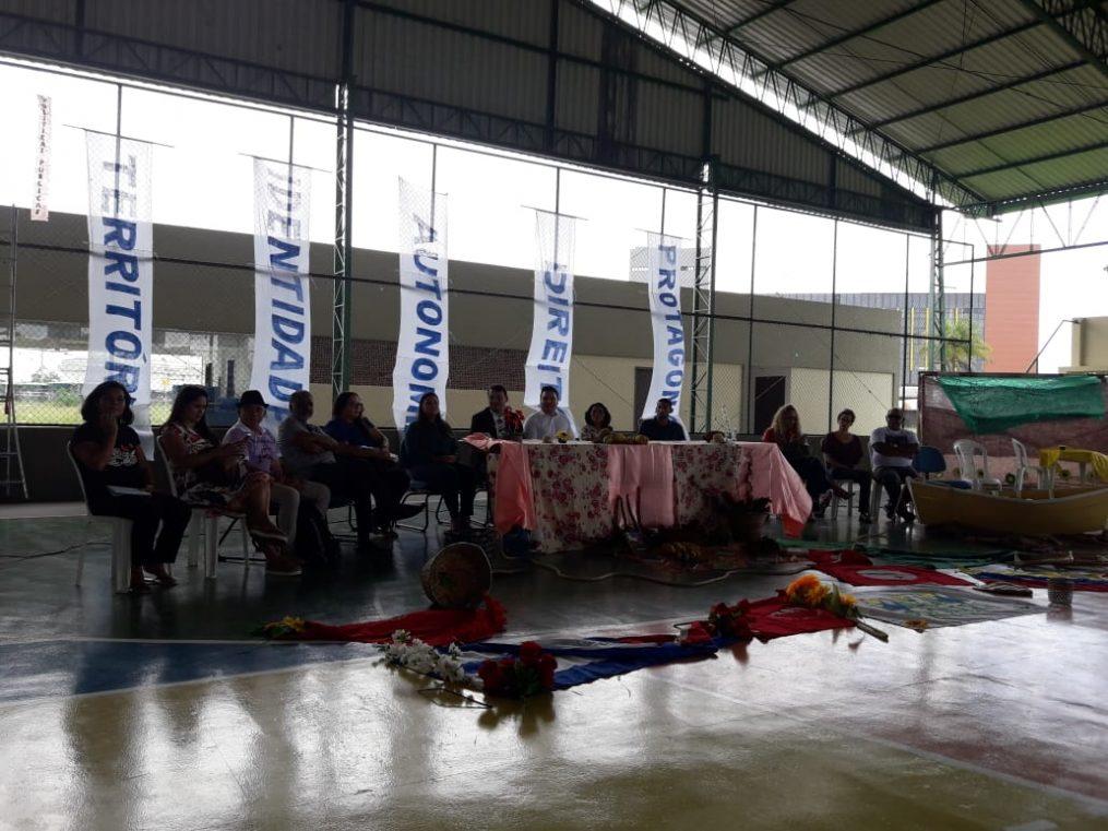 """Mesa com cerca de 10 pessoas sentadas à frente. 5 banners verticais trazem palavras como """"território"""", """"identidade"""", """"autonomia"""", """"direito"""" e """"protagonismo"""". À frente, flores enfeitam o chão."""